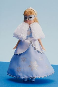 Snow Queen Lottie Doll - Lottie is thrilled to receive a party invitation to the Masked Ball. Inspired by one of her favourite stories, Lottie decides to dress as a Snow Queen. Wearing a silver, sparkly mask and a magnificent ice blue and frosty white gown studded with silver snowflakes – will any of her friends recognise her?