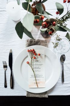 Minimalist Thanksgiving tablescape with a white linen and simple berry branches.