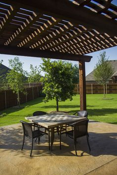 Outdoor living area right underneath a wooden arbor installed by Red Valley Landscape & Construction.