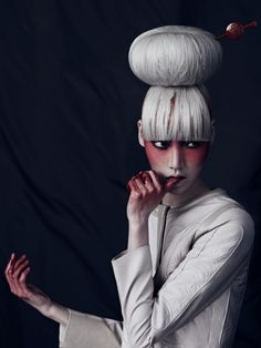 Red makeup and platinum top knot and blunt bangs. Editorial.