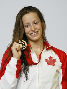 Katerine Savard of Canada holds up her gold medal after winning the Women's 100m Butterfly final on Day 2.