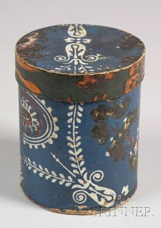 Small Wallpaper Covered Box, America, early 19th century, cylindrical form showing a building, flowers, and trees in red, green and white varnishes on a blue ground, the cover with orange and green band, ht. 5 34 in.