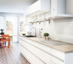 plan de travail cuisine en bois clair, armoires de cuisine et crédence blanches et carrelage de sol à motif rétro