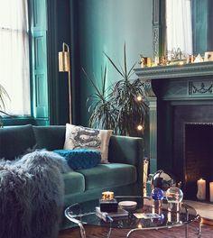 idée de peinture murale et canapé bleu pétrole, couverture de peau animal grise, cheminée gris anthracite, bougies, table basse avec plateau en verre, plante verte