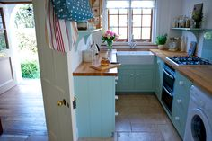 Small, compact but wonderfully bespoke English Country Kitchen by Barnes of Ashburton. Ceramic Belfast style sink and solid oak block timber top.