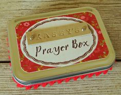 I always try to make things that I myself would love to receive or give as a gift. I am a gift fanatic! I love to give them. I love to get them. This prayer box is no exception. The tin measure 4.25 x 3.25 and is 1 deep. Each box comes with 20 pre-cut pieces of white paper for you to write your prayers on. I added some A-DOR-ABLE tiny pom pom trim just for fun! The nameplate is a piece of chipboard I have painted, hand-stamped with leather working tools, and then distressed to add some extra…