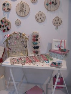 embroidery hoops to showcase smaller pieces, a birdcage and tilted display flat surface for larger ones.