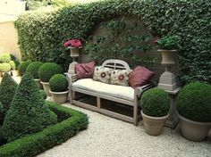 A Lutyens-style bench with cushions with pots of box topiary to either side within a topiary garden make a pleasing focal point.
