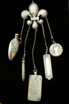 SIGNED STERLING CHATELAINE  This is a beautiful sterling silver chatelaine.  It dates c. 1880.  It has five sterling silver attachments; a perfume, a pencil, a notebook, a comb, and a pill box.  The chatelaine brooch is hallmarked.  I am not certain of the maker. *
