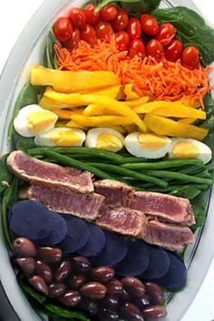 Salad Nicoise - cherry tomatoes, carrots, yellow bell pepper, boiled eggs, green beans, tuna, purple potatoes and olives on bed of spinach.