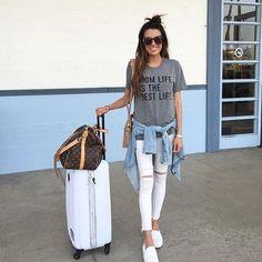 Blusa, t-shirt gráfica cinza, calça branca rasgada no joelho, jaqueta jeans amarrada na cintura, tênis branco