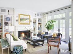 For the living room of this Winnetka home, designer Andrea Goldman placed a custom sofa covered in linen by Rogers & Goffigon and a pair of chairs from Jayson Home around a David Iatesta coffee table from John Rosselli & Associates. Living Room White, Living Rooms, Family Rooms, Living Spaces, Design Salon, White Side Tables, Custom Sofa, Living Room Inspiration, Interior Inspiration