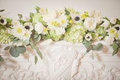 Wedding Reception flowers on classic white mantle. With gorgeous Anemones, Hydrangea, Garden Roses, Tulips and Eucalyptus. Flowers by www.hedgesdesigns.com