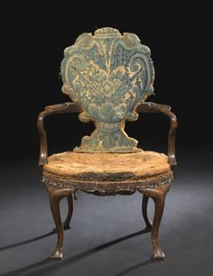 Queen Anne Walnut Side chair, first quarter 18th century, the padded shell-form back covered in period tapestry and joined by crook arms to the padded seat, raised on cabriole legs ending in squared feet, the seat having horsehair padding