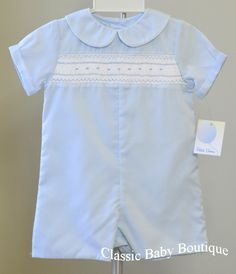 New Arrival from Boutique Designer Petit Ami. Handsome blue batiste jon jon with peter pan collar and white piping trim, lovely smocking on the chest with blue embroidery. Button back, snaps at the st