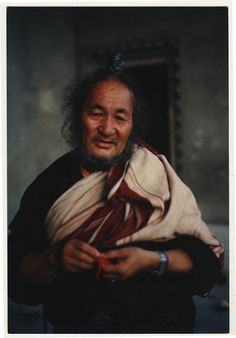 Portrait of Ngawang Chodrub Rinpoche-Tibetan Buddhist Nyingma master and ngakpa holding a blessing cord, wearing a top knot and Adi-Tharlam Monastery porch, Boudha, Kathmandu, Nepal, 1990.