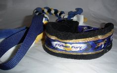 """These leads bring your dog to the ring with style, class....and play! Each features a padded neck piece, complimentary background ribbon, and an attached lead with a tug securely braided around it for instant play, leading out to a nylon web handle for security in holding your dog.    Flyball Fury - Neck piece 15"""" to 21"""", tug is blue, black, white and yellow  Frozen - Neck piece 15"""" to 21"""", tug is 2 shades of blue, 2 shades of purple  Geometric - Neck piece 14"""" to 20"""", tug is red, white…"""