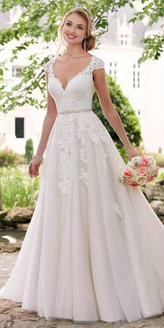 This romantic cap sleeve wedding dress with cameo back from Stella York is a sweet reminder of feminine style. Matte lace creates a shadow effect throughout the tulle skirt bringing dramatic volume and subtle interest to this A-line wedding dress. The flattering waist is drawn in by a crystal belt and deep sweetheart neckline that is finished by swirls of organic edge lace – for a truly unique dress! Fabric buttons over an easy-to-close zipper allow the butterfly lace motif to shine.