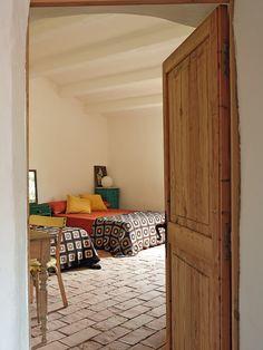Ganchillo - AD España, © Montse Garriga En otro dormitorio, colchas de ganchillo, silla de colegio y mesa de pino lavado. La puerta de madera es recuperada. Foto Montse Garriga
