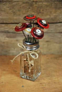 """Pipe cleaner """"flowers"""" instead of buttons, or maybe make wire into curlicues to hold kids' school photos."""