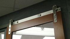 Stainless steel hardware looks sharp on this office barn door.