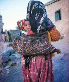 A Shavak tribeswoman in Tunceli carrying a baby in a 'turik' kilim baby carrier. Mother And Child Reunion, Arabian Women, The Kurds, Baby Carrying, Young Old, Asian Kids, People Of The World, Mothers Love, Mom Style