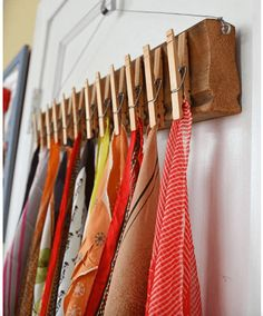 With just a shortened piece of molding, a couple of eye hooks, wire and wooden clothes pins, you too can make this very scarf hanger in no time at all.