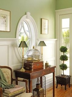 Room with light green walls, white wainscoting and an oval window -- Private residence, Kittery, ME -- photo by Richard Mandelkorn -- New England Home Magazine, May/June 2006
