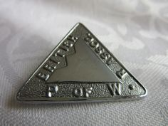 A silver metal triangular badge with British P of W.R Assoc. stamped around the edge. I would guess it dates from around the late 1940s to 1950s but it is only a guess. It measures 3.2 cms across. | eBay!