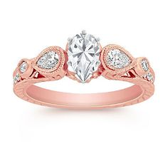 Three-Stone Vintage Pear Shaped and Round Diamond Engagement Ring in Rose Gold with Pear Diamond. As part of our Annata collection, this cultured vintage inspired engagement ring features two stunning pear-shaped diamonds, at approximately .28 carat TW, and 18 round diamonds, at approximately .17 carat TW. Set in quality 14 karat rose gold with gorgeous hand-engraved and milgrain detailing, the total carat weight is approximately .45 carat.