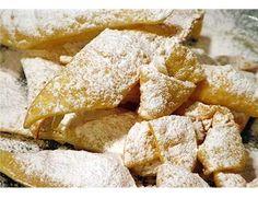 Chiacchiere di Carnevale: ingredienti sono 400 g di farina, 3 uova, 50 g di zucchero, 50 g di burro, 1/2 bicchierino di liquore (vin santo, vino bianco, marsala), 1 pizzico di sale, zucchero a velo, scorza di 1/2 limone grattugiata, olio di semi q.b.
