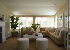 beautiful transitional living room with camel L shaped sectional sofa, pair of round white ottomans, fiddle leaf fig plant and sisal rug (Lynn Morgan Design)