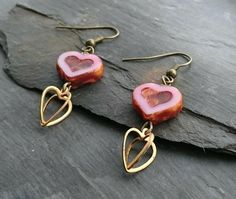 These pretty earrings feature glass heart shaped beads in a delicate shade of pink, and heart shaped charms. These have been attached to simple antique gold coloured ear wires. The earrings have a drop of just over one inch. Your earrings will arriv. Handmade Jewellery, Earrings Handmade, Organza Gift Bags, Heart Charm, Antique Gold, Heart Shapes, Delicate, Charmed, Drop Earrings