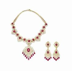A SET OF RUBY AND DIAMOND JEWELRY, BY VAN CLEEF & ARPELS Comprising a necklace, suspending a detachable cartouche-shaped pendant, centering upon an oval-cut ruby within a circular and baguette-cut diamond surround, with a pear-shaped ruby fringe, from a band set with a series of alternating ruby and diamond cartouche and oval openwork links, to the circular-cut diamond backchain; and a pair of ear pendants en suite, mounted in gold.