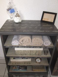 French Script Dresser  Remove drawers and cross members, Paint it in a coal color and add the French Script all over the entire piece. 4 pieces of MDF cut to fit into the spots where the old drawers used to be. Now it is a perfect piece for bath towels or baskets.