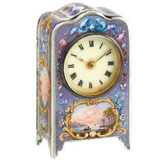 Miniature Silver and Enamel Desk Clock  The miniature silver clock with serpentine top centering a circular ivory-tone dial with black Roman numerals, the whole applied with patterned lavender enamel, set throughout with enameling of sunset landscapes and floral decoration, key-wind, key-set, 3/4 plate Swiss movement, no. 12413, case with English hallmark, no. 2268, circa 1930. 1 1/16 x 1 7/8 x 11/16 inches.