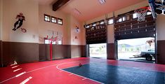 Indoor Sports Court with special flooring, basketball hoops, and garage door…