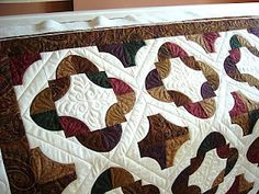 Drunkard's path quilt.  Love the dark, rich colors she chose.  Beautiful machine quilting too