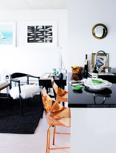 Kitchen island with black marble, copper chairs, furry black chair, and black and white photo art