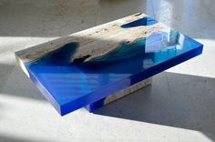 Beautiful coffee tables made out of carved travertine limestone and layers of transparent blue resin that looks like crystal clear ocean water by La Table.