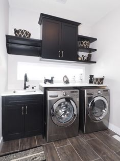 Small laundry room with wood grain tile floor, black cabinets and shelving and white countertops | Tiffany MacKinnon