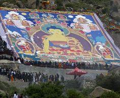 Monaci buddisti al lavoro per la realizzazione di un gigantesco dipinto religioso durante lo svolgimento del Sho Dun Festival al monastero di Drepung nella città di Lhasa, in Tibet. Il festival annuale conosciuto anche come Festival dello Yogurt è uno dei più importanti festival di Lhasa per spettacoli folcloristici tibetani, opere liriche e altri eventi.