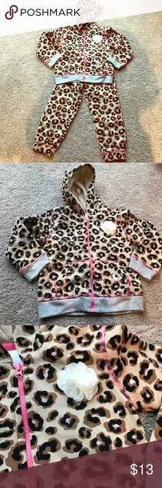 Adorable, never worn, toddler leopard track suit! Super cute, never worn, toddler leopard track suit with pink trim, and a flower accent. Sweatshirt is hooded with a zip down front. Pants have a drawstring closure. Both pieces are lined and snugly. Size 3T. Wonder Kids Matching Sets