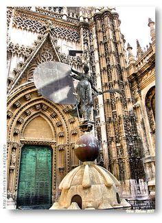 "SEVILHA: O ""Giraldillo""  O ""Giraldillo"" é o nome popular da escultura que encima a torre Giralda de Sevilha. O nome verdadeiro é ""Triunfo da Fé Vitoriosa"". Muitas vezes é também erroneamente designada como Santa Joana."