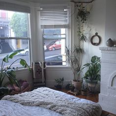 white on white bedroom with cozy blanket and plants
