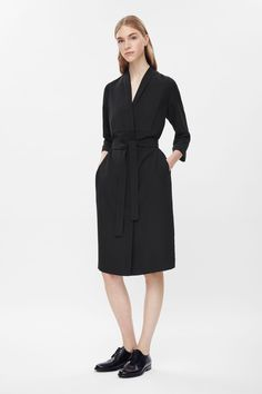 Based on the shape of a blazer, this long dress is made from lightweight fabric with a contrast textured bib on the front. A straight shape that comes in at the waist with a tie fastening, it has slim fade-out lapels, deep v-neckline and hidden buttons along the front.