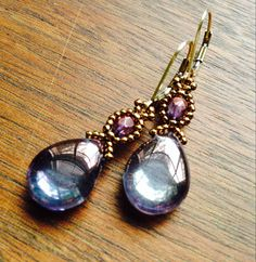 These stunning luminous earrings are woven with bronze seed beads and purple czech glass teardrop beads, and finished with 14k gold-filled