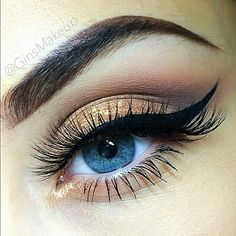 Gold glitter eye makeup with dramatic cat eye liner