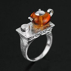 Believe it or not, this charming little teapot is handcrafted out of natural amber. Sterling silver sets on the amber forming it's handle, teapot cover and spou
