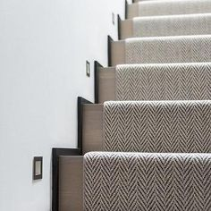 A woven herringbone rug accents a gray wash staircase illuminated by inset light… - Modern Carpet Staircase, Staircase Runner, Interior Staircase, Staircase Remodel, Staircase Design, Herringbone Rug, Design Living Room, Hallway Designs, White Carpet